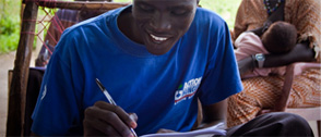 smiling boy writing in notebook