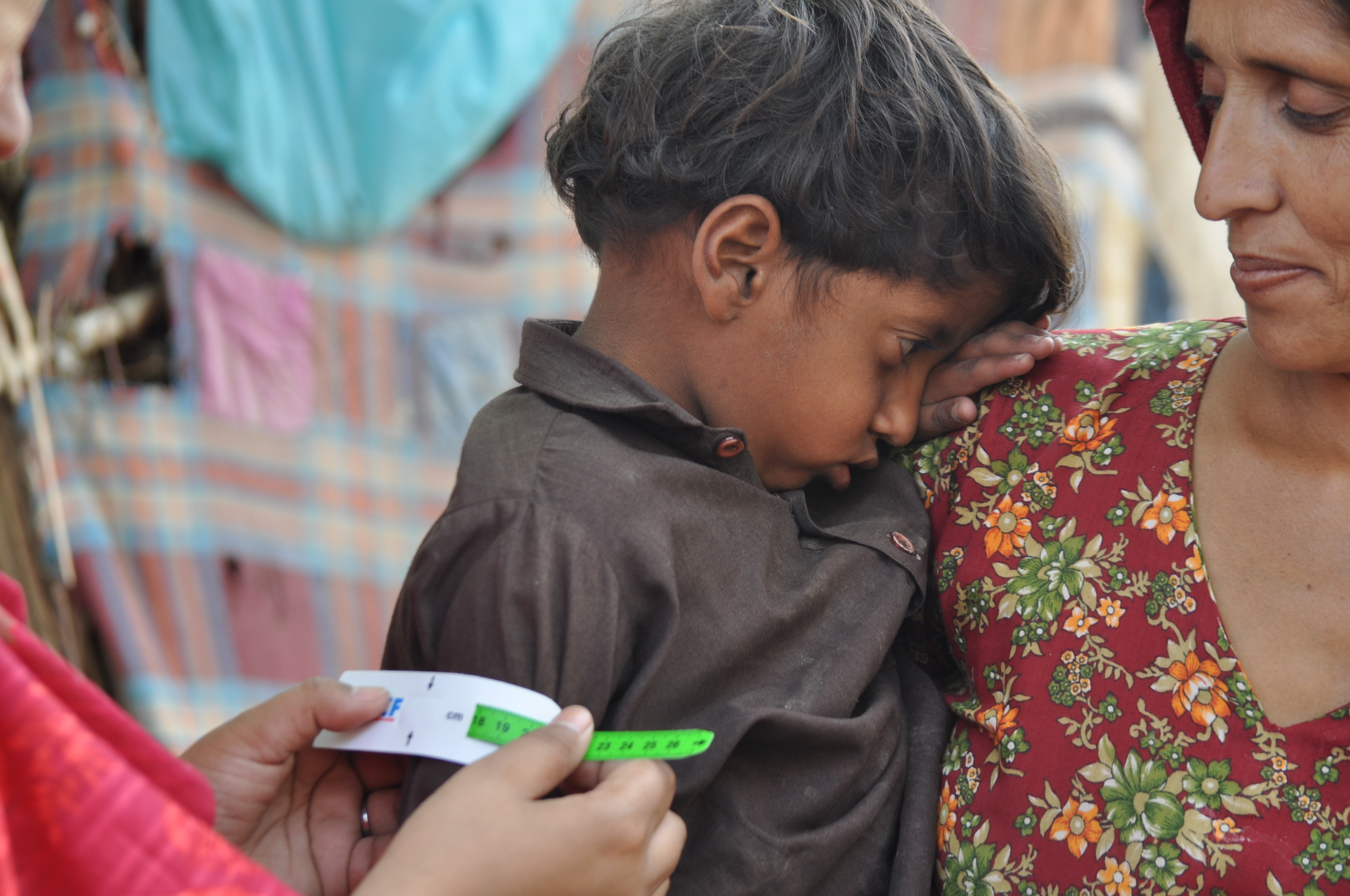 A middle-upper arm circumference (MUAC) test is administered on a child in Dadu. Photo: Z. Metlo