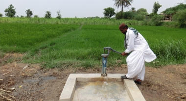 A man pumps water from his village's rehabilitated borehole. Photo:C.Brett