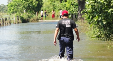 An ACF-Americas worker walks through floodwater to help Guatemalans.