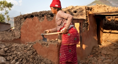 A woman clears the stones that once made up her home in the village of Chaughada in Nepal's Nuwakot district, northwest of Kathmandu. Credit Agnes Agnes Varraine-Leca for Action Against Hunger
