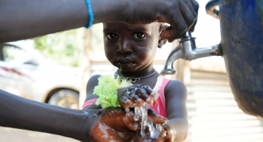 A South Sudanese girl washes her hands with clean water.
