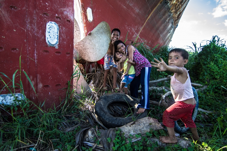 Roselyn Omeres (center) plays with her younger brothers and sisters near a capsized ship outside Tacloban. Photo: ACF-Philippines, D. Burgui