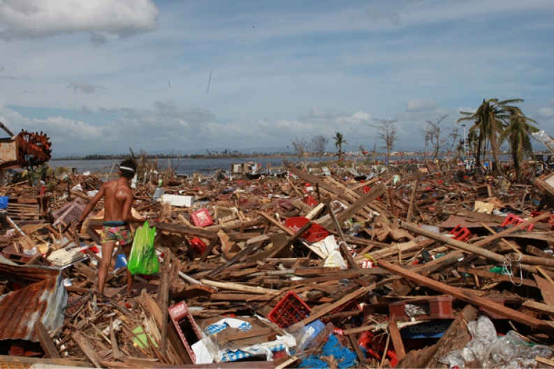 A typhoon survivor walks through debris in Tacloban. ACF-Philippines, J. Maitem