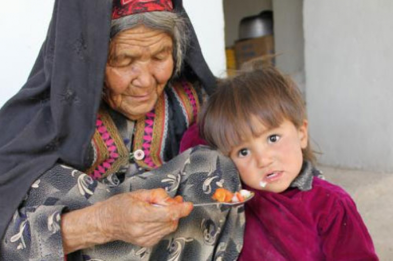 Zainab feeds her 3-year-old grandson vegetables from their home garden. Photo: ACF-Afghanistan