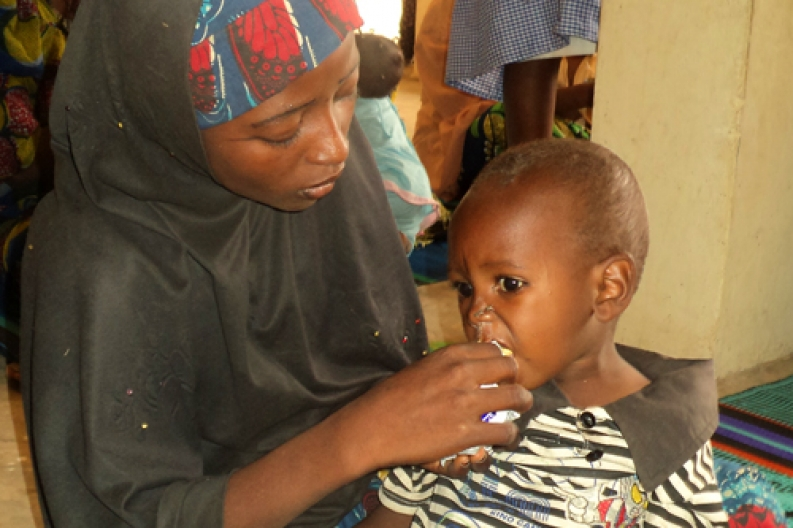 A mother in Nigeria feeds her son therapeutic food at a community health center. Photo: ACF-Nigeria.