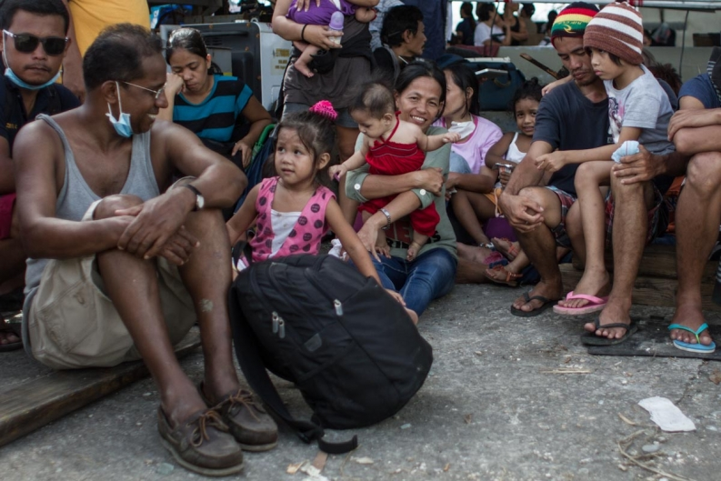 Sam Mutthar, left, and his wife, center, sit with their family and friends at Tacloban airport. Photo: ACF-Philippines, Daniel Burgui Iguzkiza