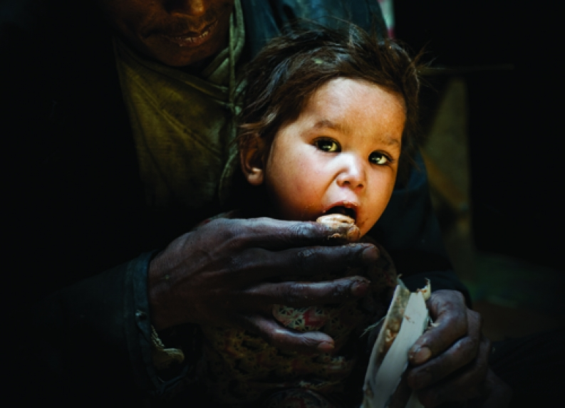 A malnourished child is fed therapeutic food by her father. ACF-Nepal, courtesy S. Remael.