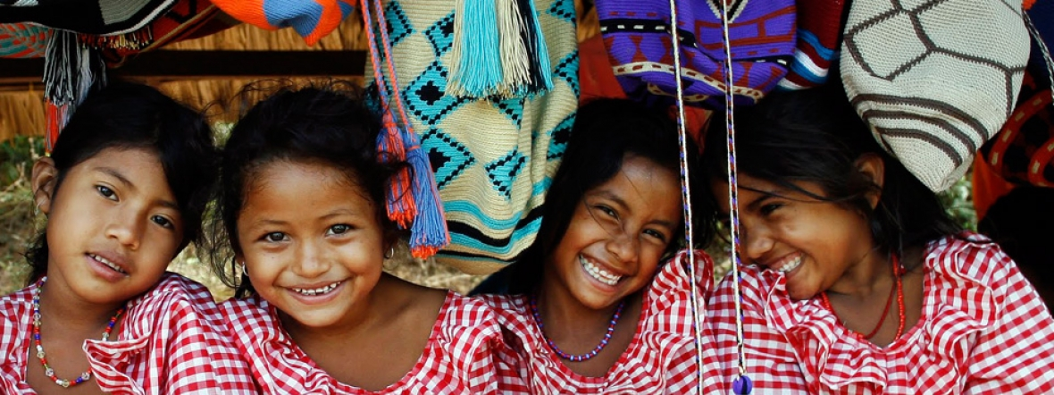 Young girls sit at a market stall in Colombia.