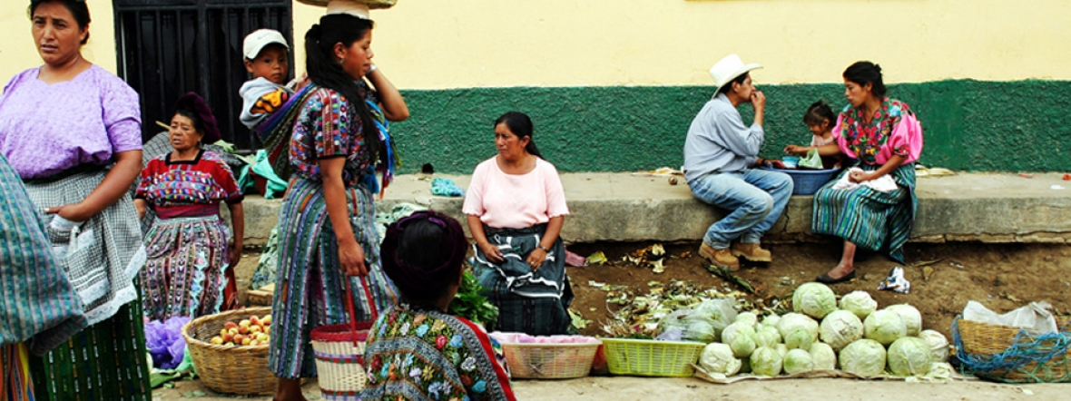 Women sell vegetables and other products in a market in Guatemala.