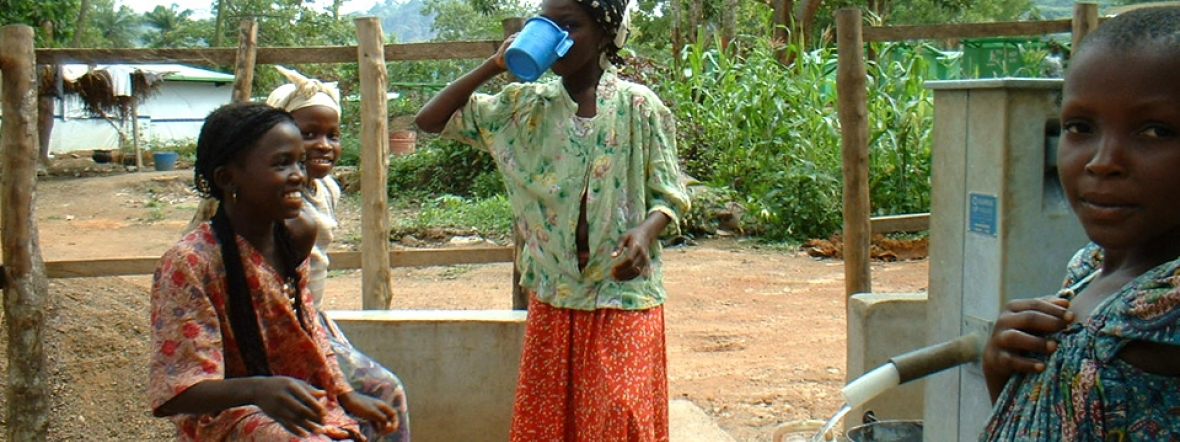Girls in Guinea drink clean water from a village well.