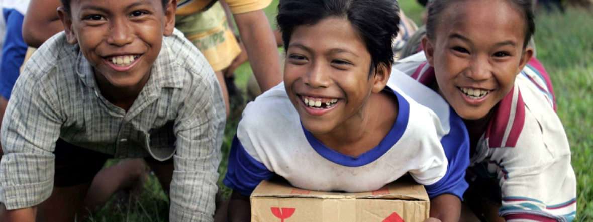 Displaced children in Indonesia receive emergency food supplies after a tsunami.