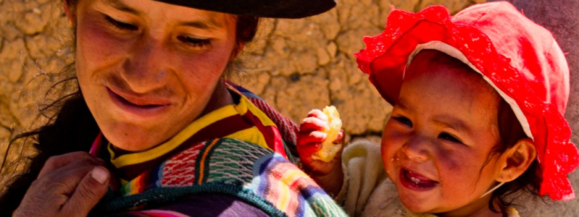 A mother feeds her young child fortified crops in Peru.