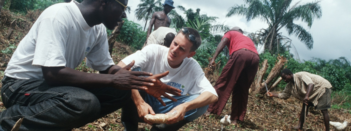 An Action Against Hunger staff member works with local farmers in Sierra Leone.