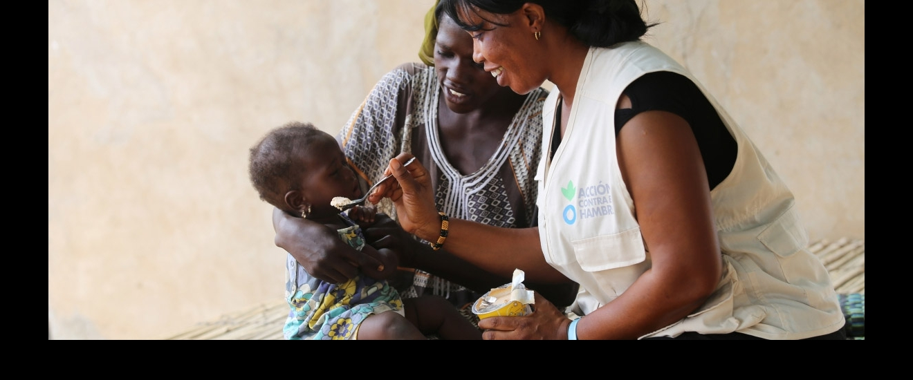 Action Against Hunger aid worker helping a malnourished child