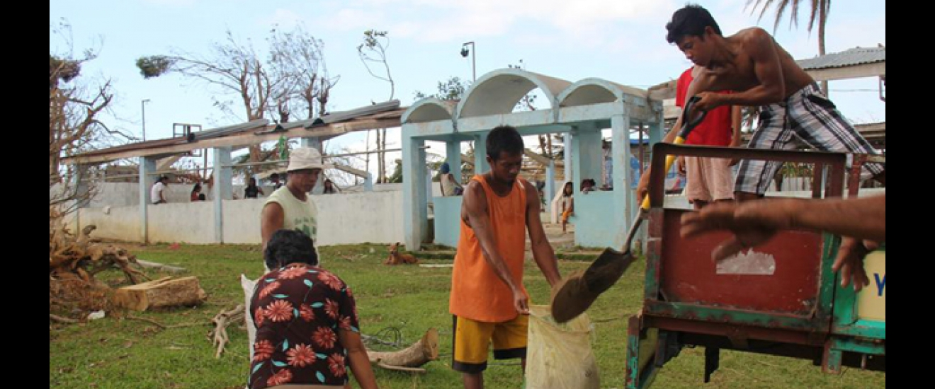 Villagers in Dayhagan shovel sand for the water tap's foundation. Photo: ACF-Philippines, L. Grosjean