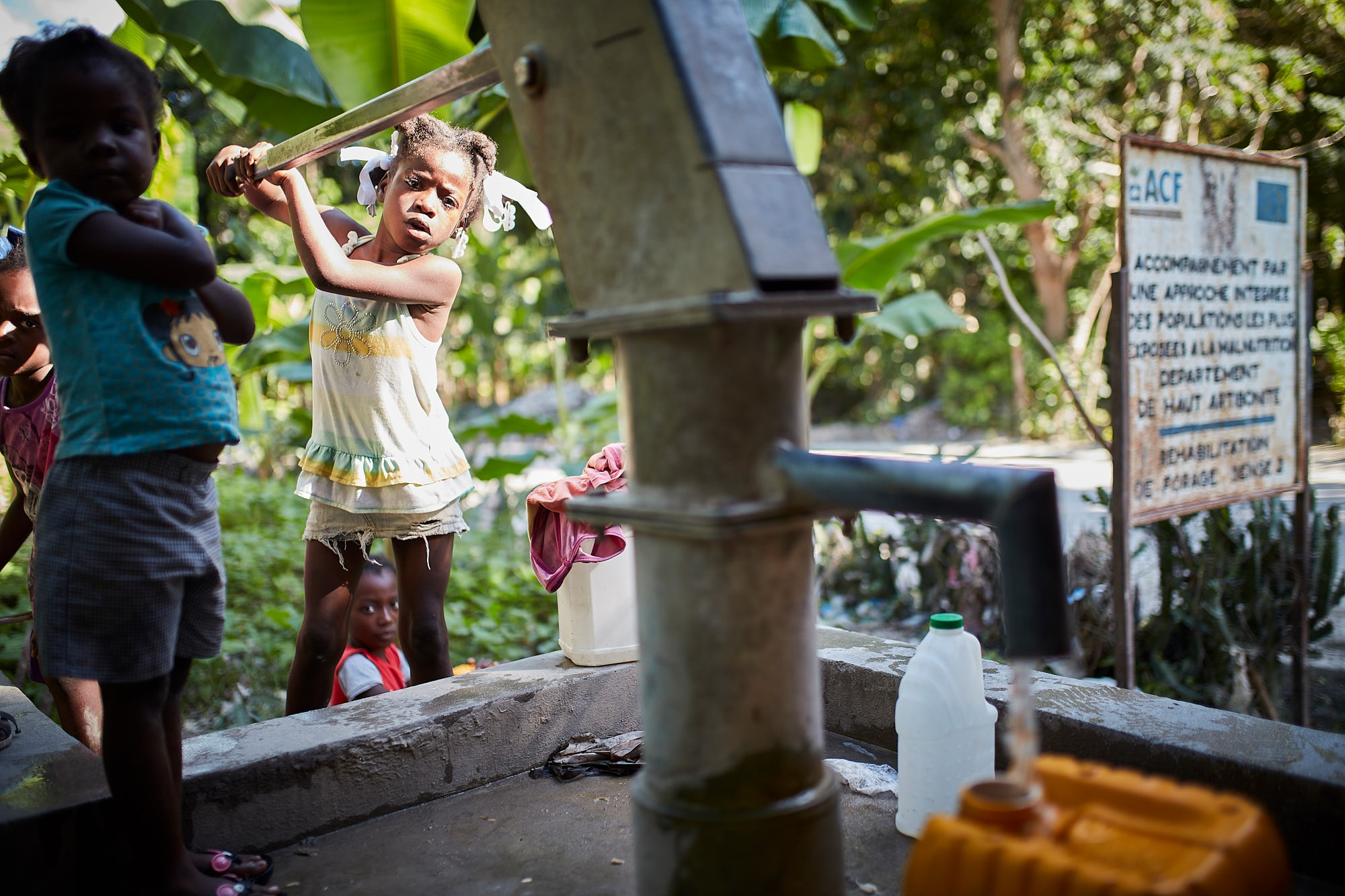 A girl pumps water at a water point installed by Action Against Hunger in 2008.