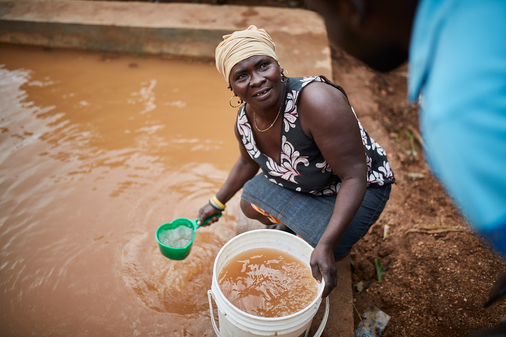 A local woman pictured next to a pond, dug to provide water storage in the dry months.