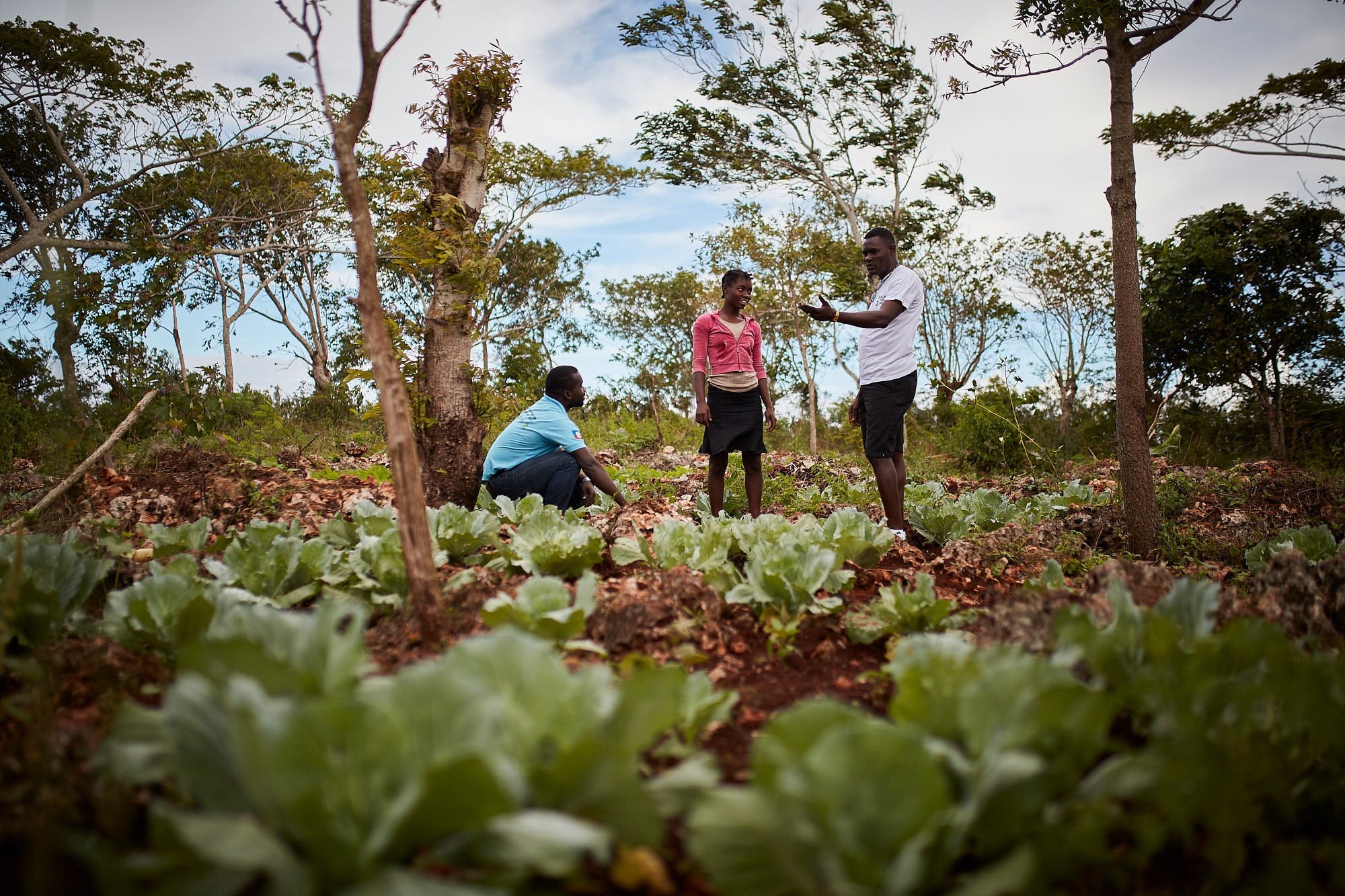 Action Against Hunger staff pictured with a farmer in his microgarden.