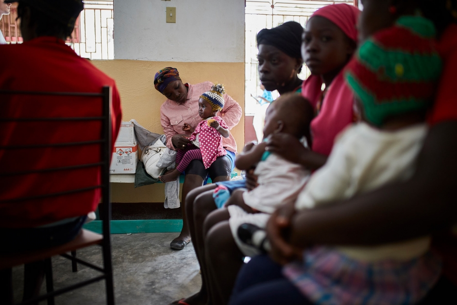 A mother and child waits for screening at the health center.