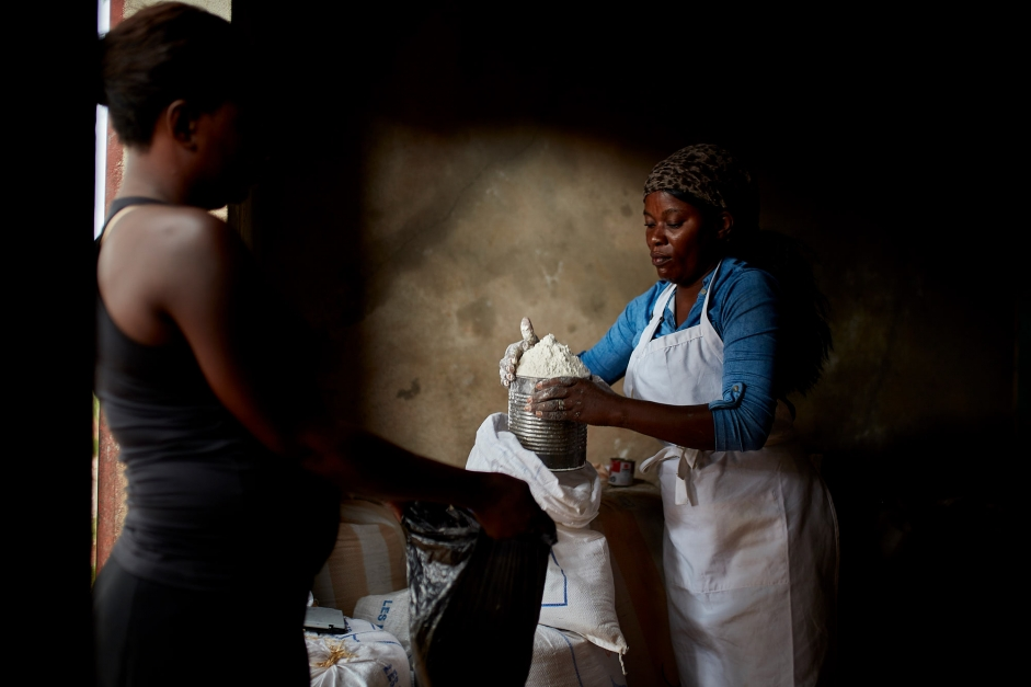 A woman uses her food vouchers to purchase flour from a local merchant.