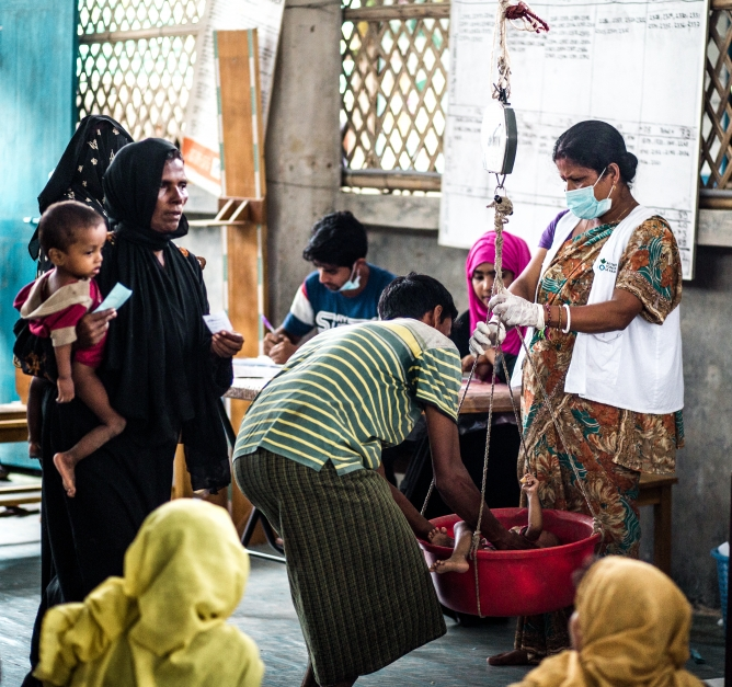 Rohingya mothers bring their children to be weighed as part of a malnutrition screening. Our teams estimate that among newly arrived refugees in Cox's Bazar, 6% of children under 5 are severely malnourished. Photo: Kathleen Prior for Action Against Hunger, Bangladesh