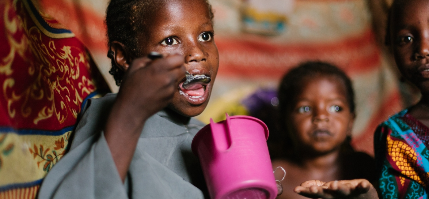A displaced girl eats a nutritious meal cooked by the Porridge Moms, an Action Against Hunger initiative in Northeast Nigeria supported by the U.S. Government's Food for Peace program.