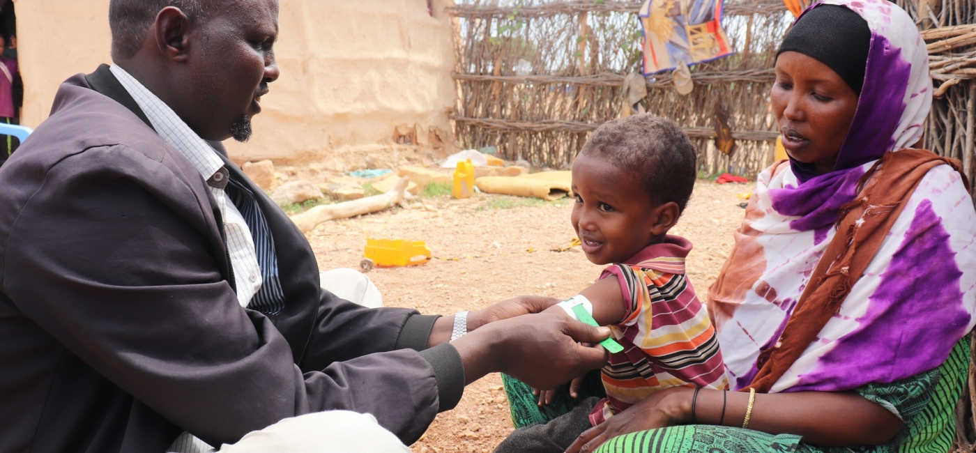 As his wife Kafiyo watches, Abdullahi measures his son Khalid's mid-upper arm circumference to check his nutrition status.