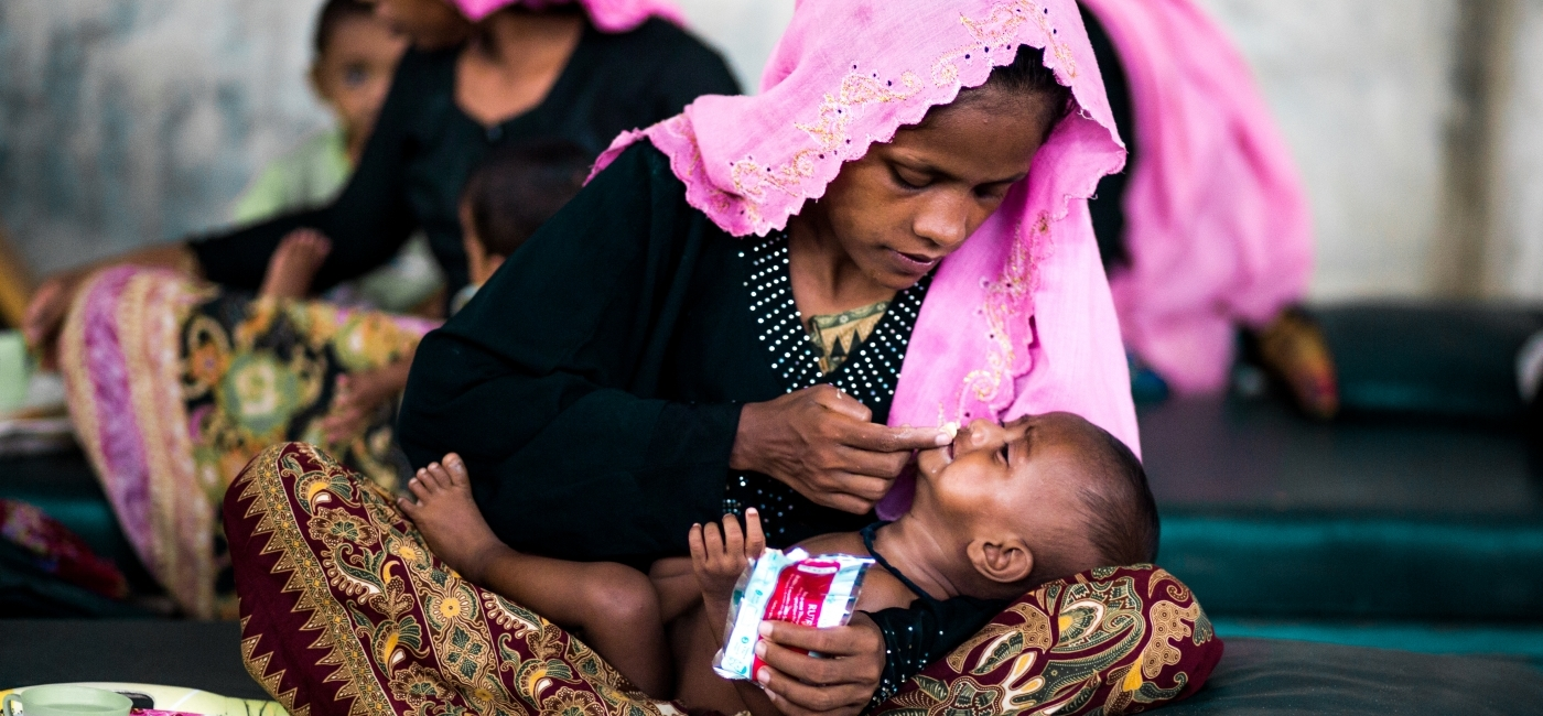 A mother feeding her child in a refugee camp