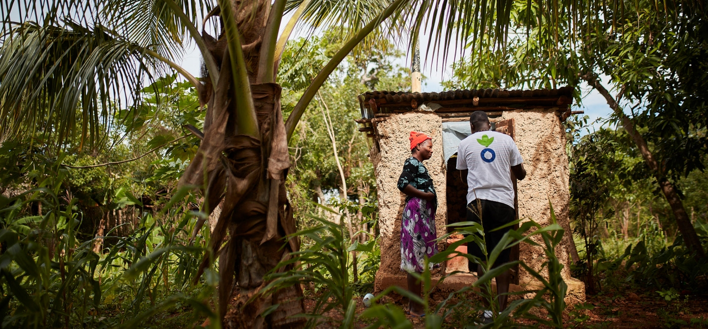 An Action Against Hunger team member speaks with a woman outside of a latrine.