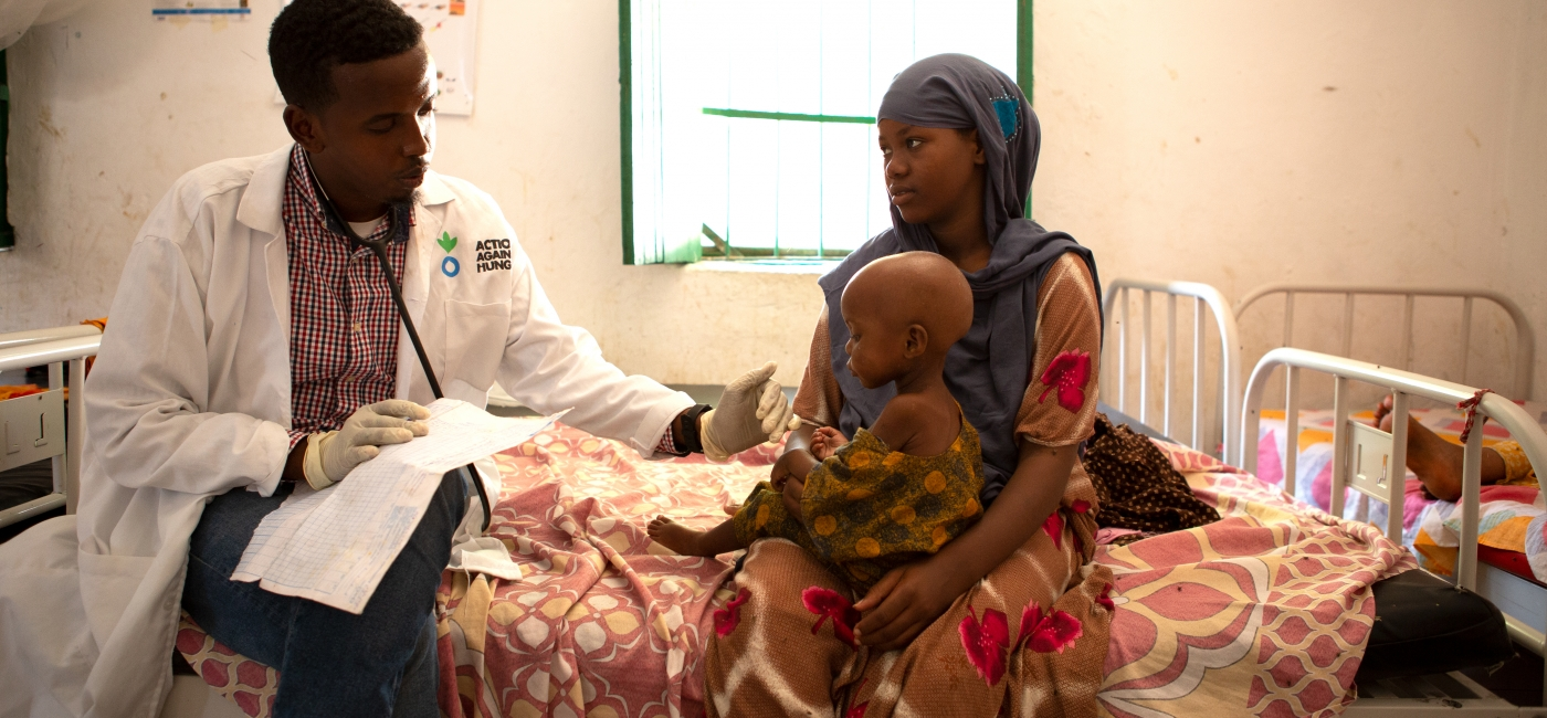 A doctor performs a routine health check up on young girl at one of Action Against Hunger's Stabilization Centers in Mogadishu.