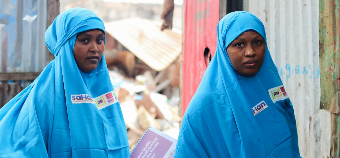 Two Female Community Influencers, Fardosa (left) and Amina (right), pose before they head into a home to meet with a mother.