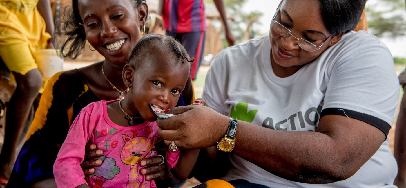 Dieymaba Niang sits while her daughter Kadia Diallo is fed ready-to-use therapeutic food to regain her health. Together, we can save lives and help children like Kadia not only survive - but thrive.