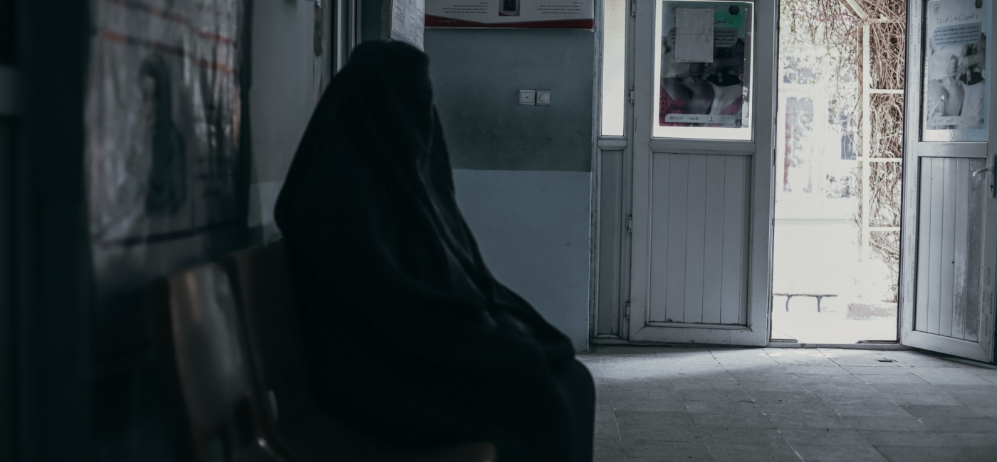 A woman waits for care in a health center in Afghanistan.