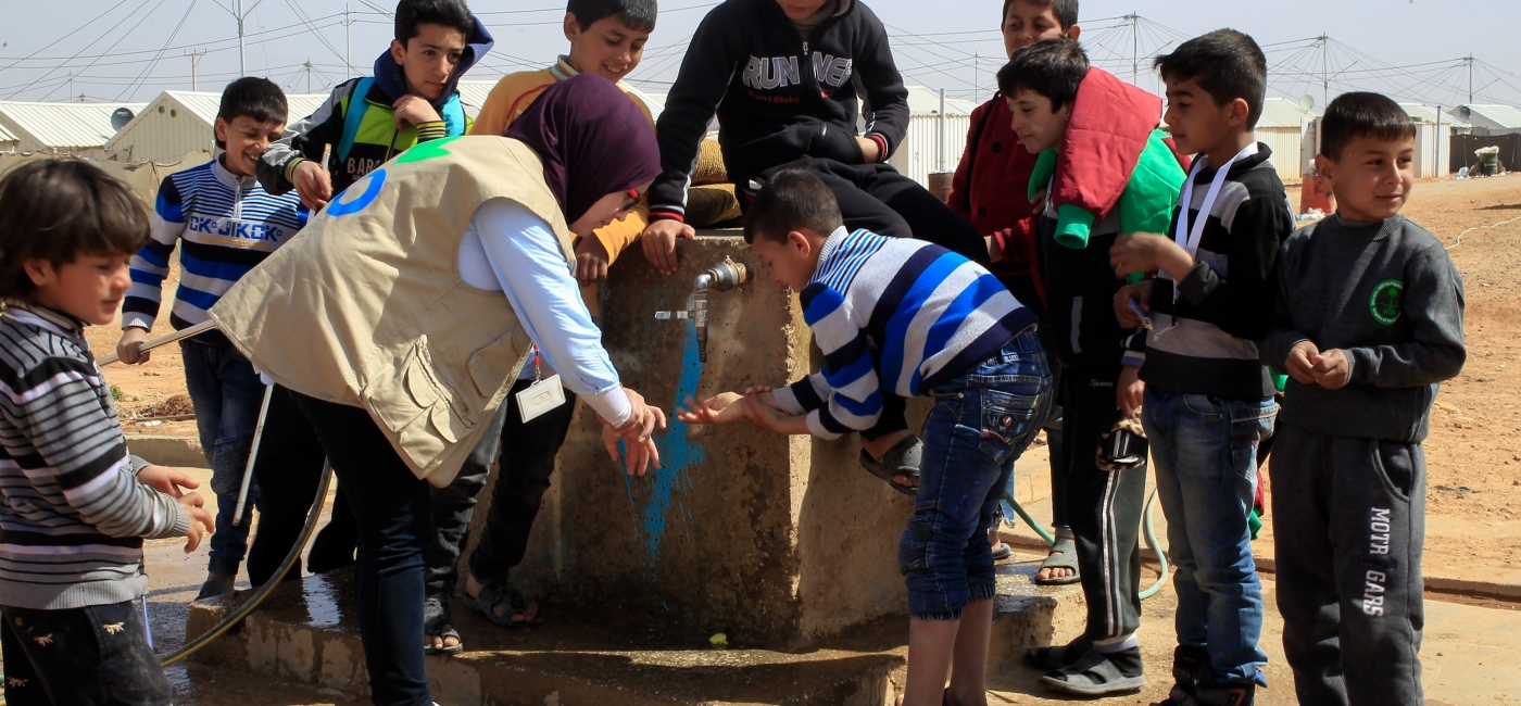 A member of Action Against Hunger's WASH team teaches children about hygiene and handwashing in Azraq Refugee Camp.