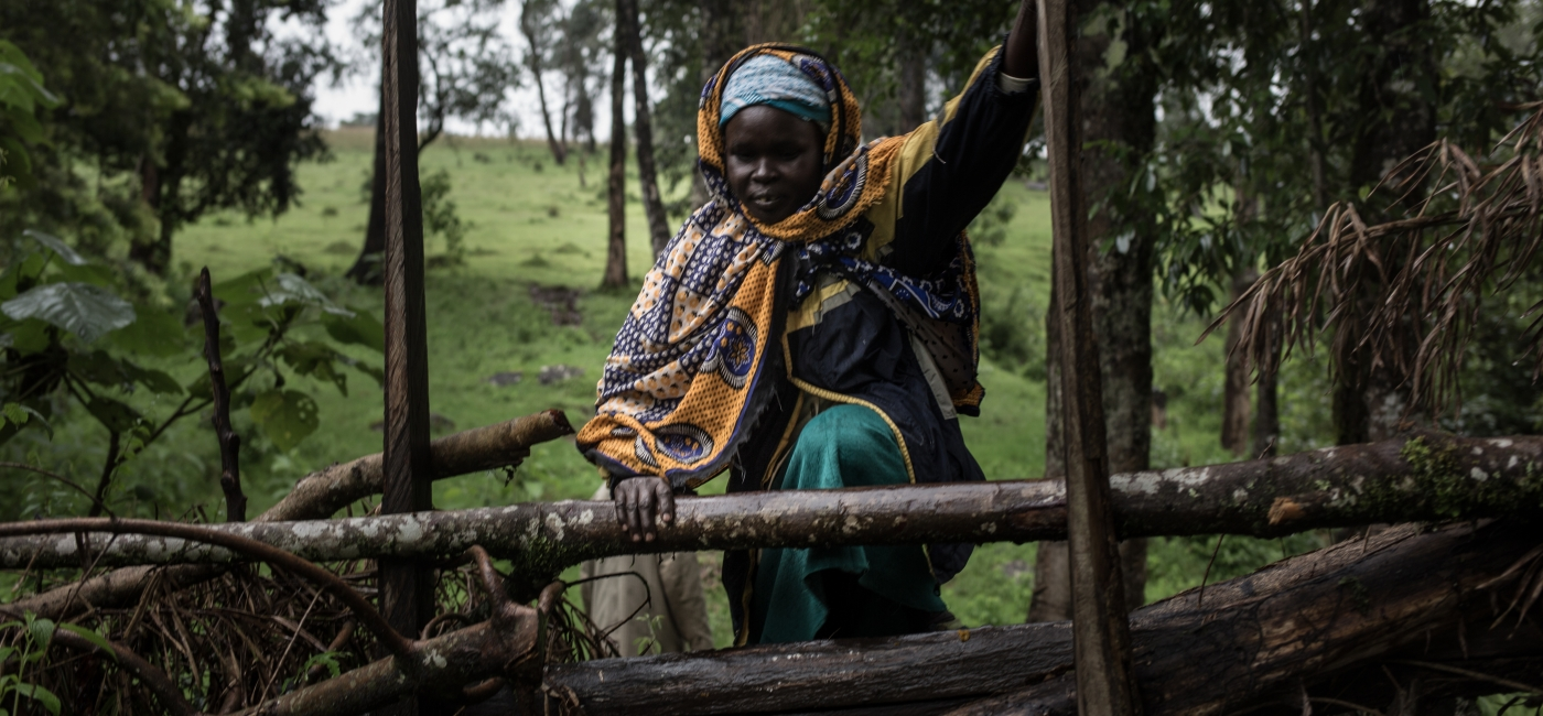 Clementine, community health volunteer in West Pokot, Kenya, hops a fence as she travels from home to home, checking on families in her district.
