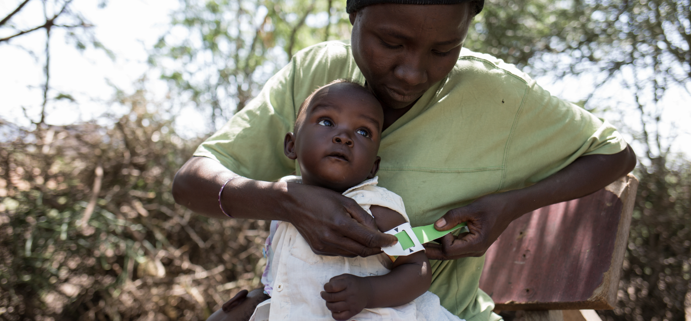 Elisabeth measures her daughter's nutrition status using a simple tool called the Mid-Upper Arm Circumference (MUAC) band