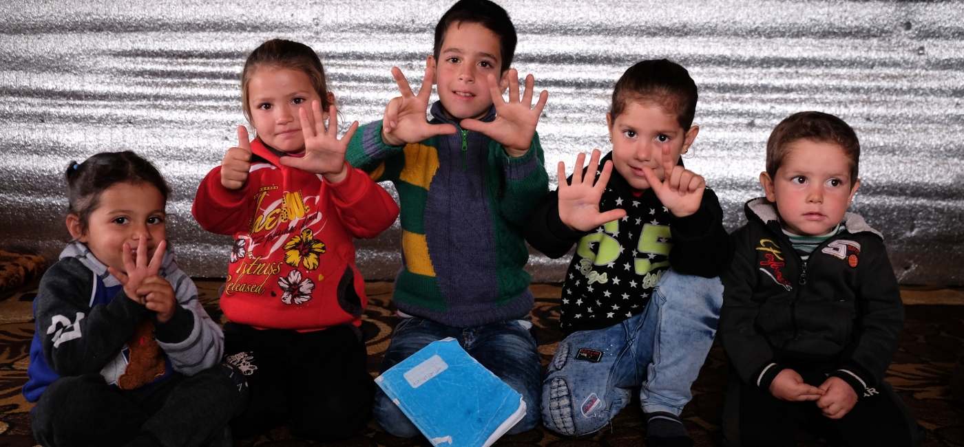 Ali, middle, and his siblings use their fingers to share their ages. Their family is from Raqqa, Syria, and fled to Lebanon as refugees last year.