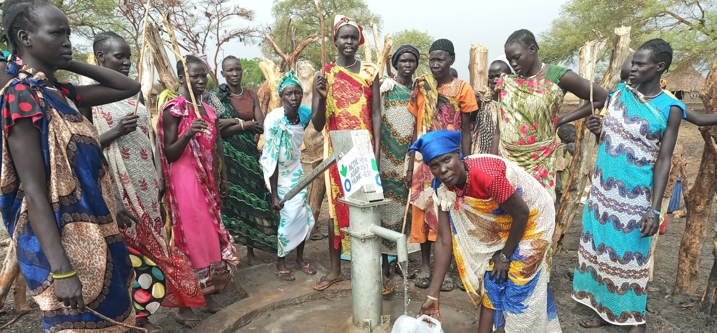 Women gather around a repaired water point in South Sudan.