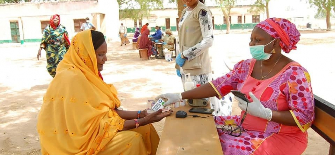 Action Against Hunger staff give out cash transfers.
