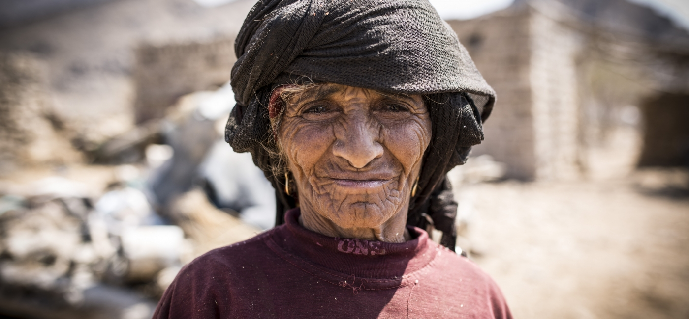 In Yemen, a woman stands in front of her community, which has been destroyed by conflict.