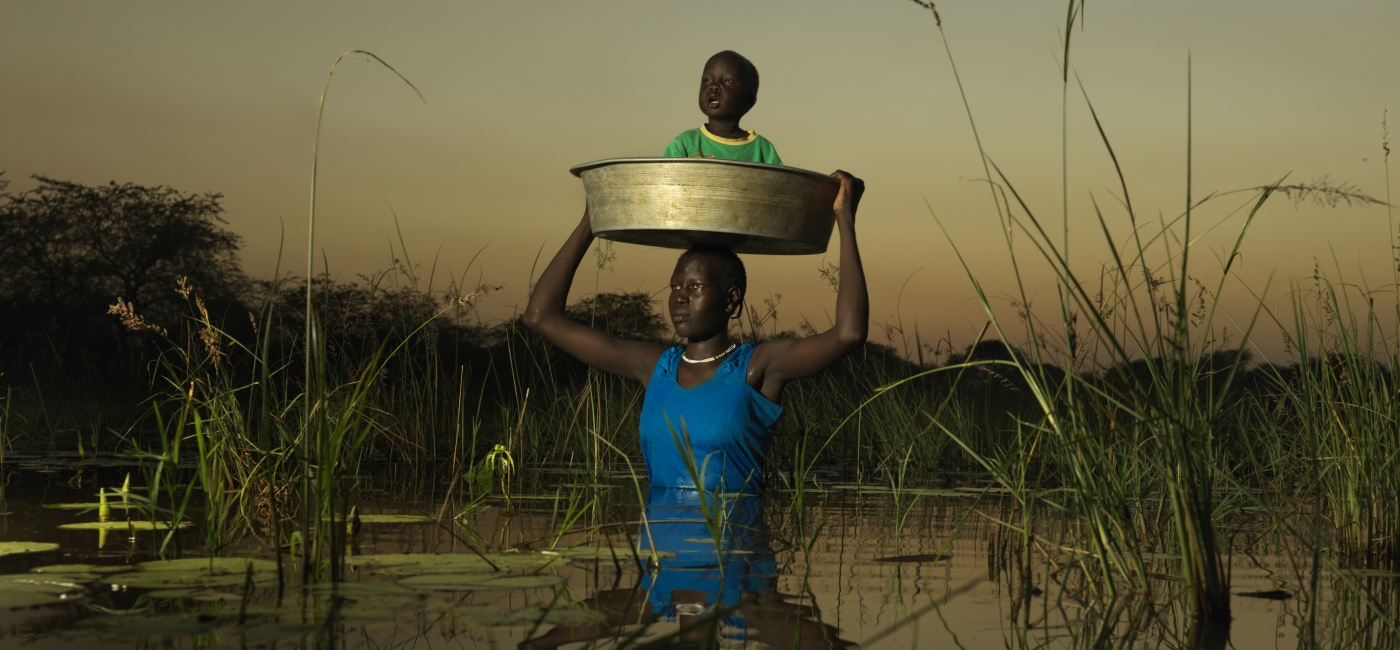 After the worst flooding in decades, mothers in Old Fangak, South Sudan, carried their children in buckets to dry land.