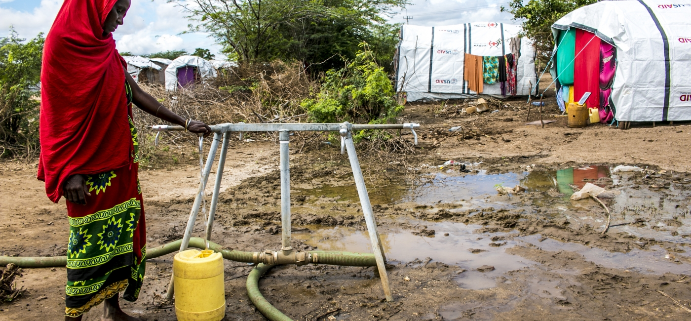 A woman fills a jerrycan with clean water at a water point installed by Action Against Hunger in Bandi Camp, Kenya.