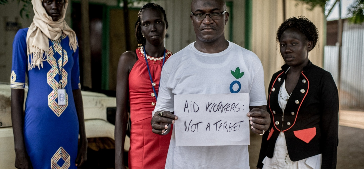 Action Against Hunger staff in South Sudan hold signs to advocate for stronger protection of aid workers.