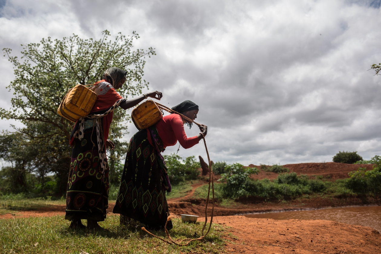 Gordo and another woman from her community collect water.