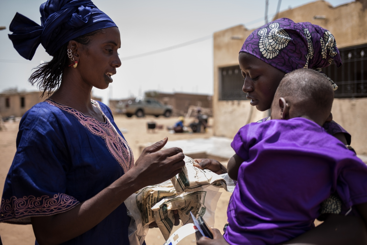 A mother receives enriched flour, made from local cereals with mineral and vitamin supplements.