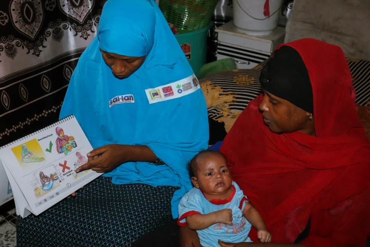 Amina listens during a health education session with her newborn at home.