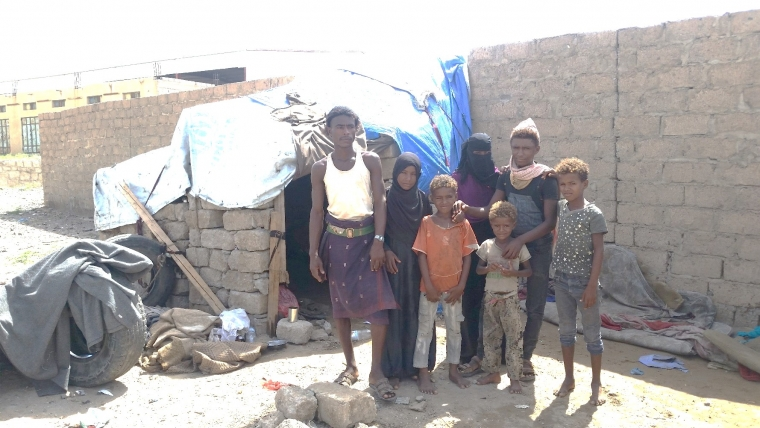 Hasan and his children in front of the shack he built for them to live in.