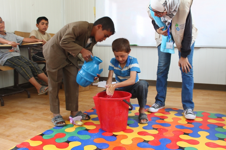 Action Against Hunger's team teaches Syrian refugee children how to wash their hands effectively in Azraq Camp.