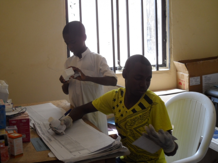 Bulama helps prepare medicines at the health center with his supervisor.